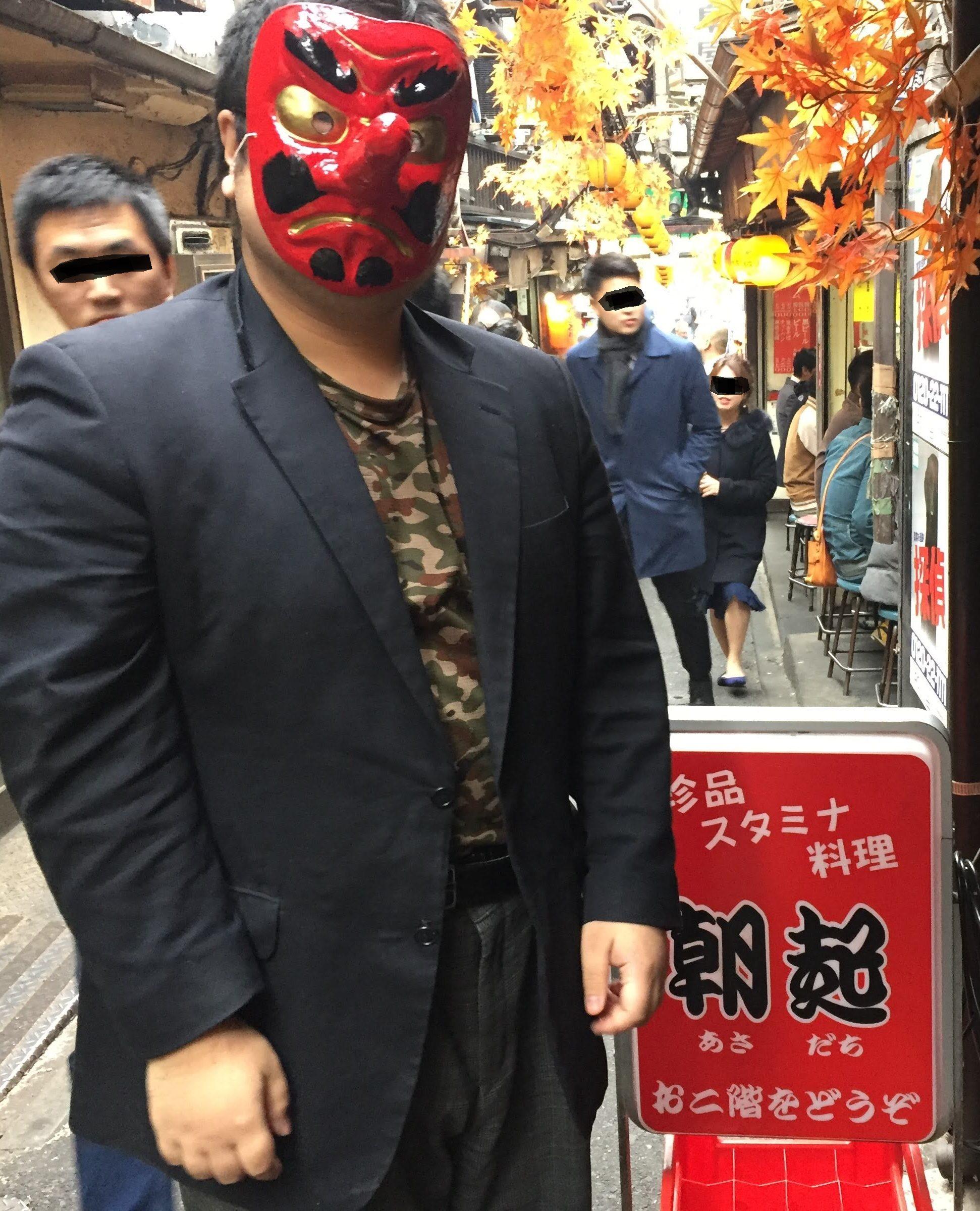 新宿の「朝起」店の前で天狗のお面をかぶるダースー
